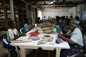 Women hand rolling clay beads at Kazuri